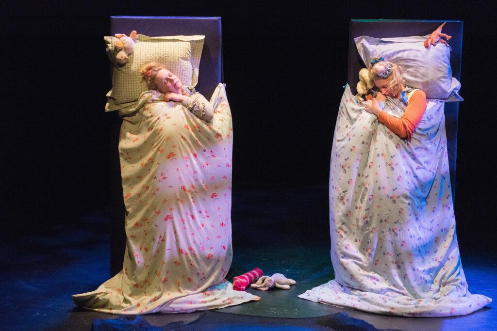 Kaksi näyttelijää nukkuvat pystyyn nostetuissa sängyissään.
