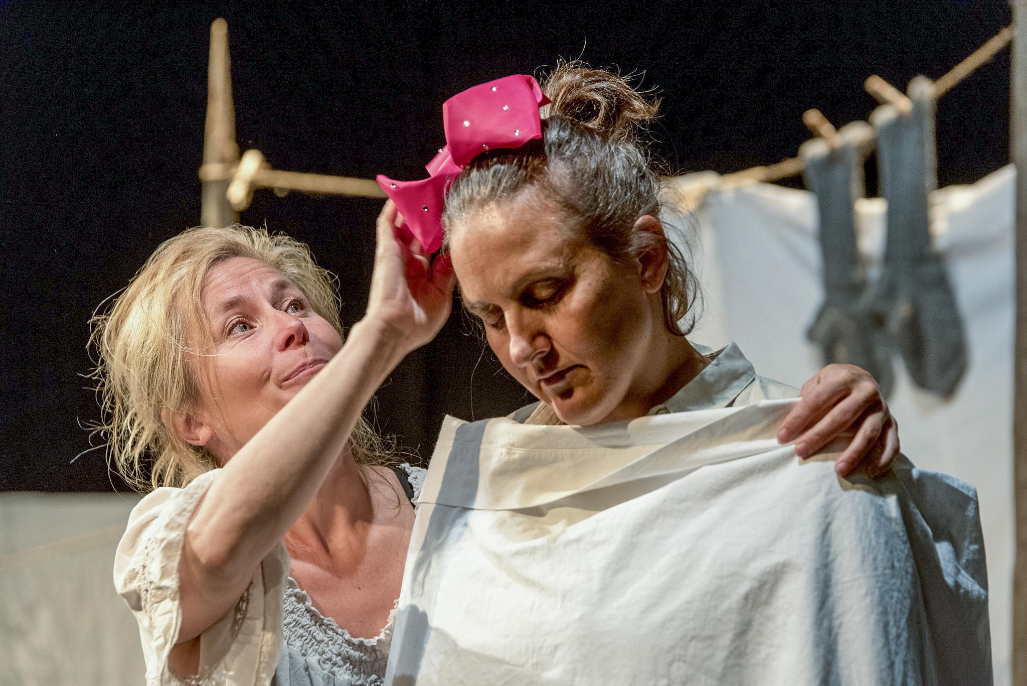 Nainen asettelee rusettia toisen naisen päähän.