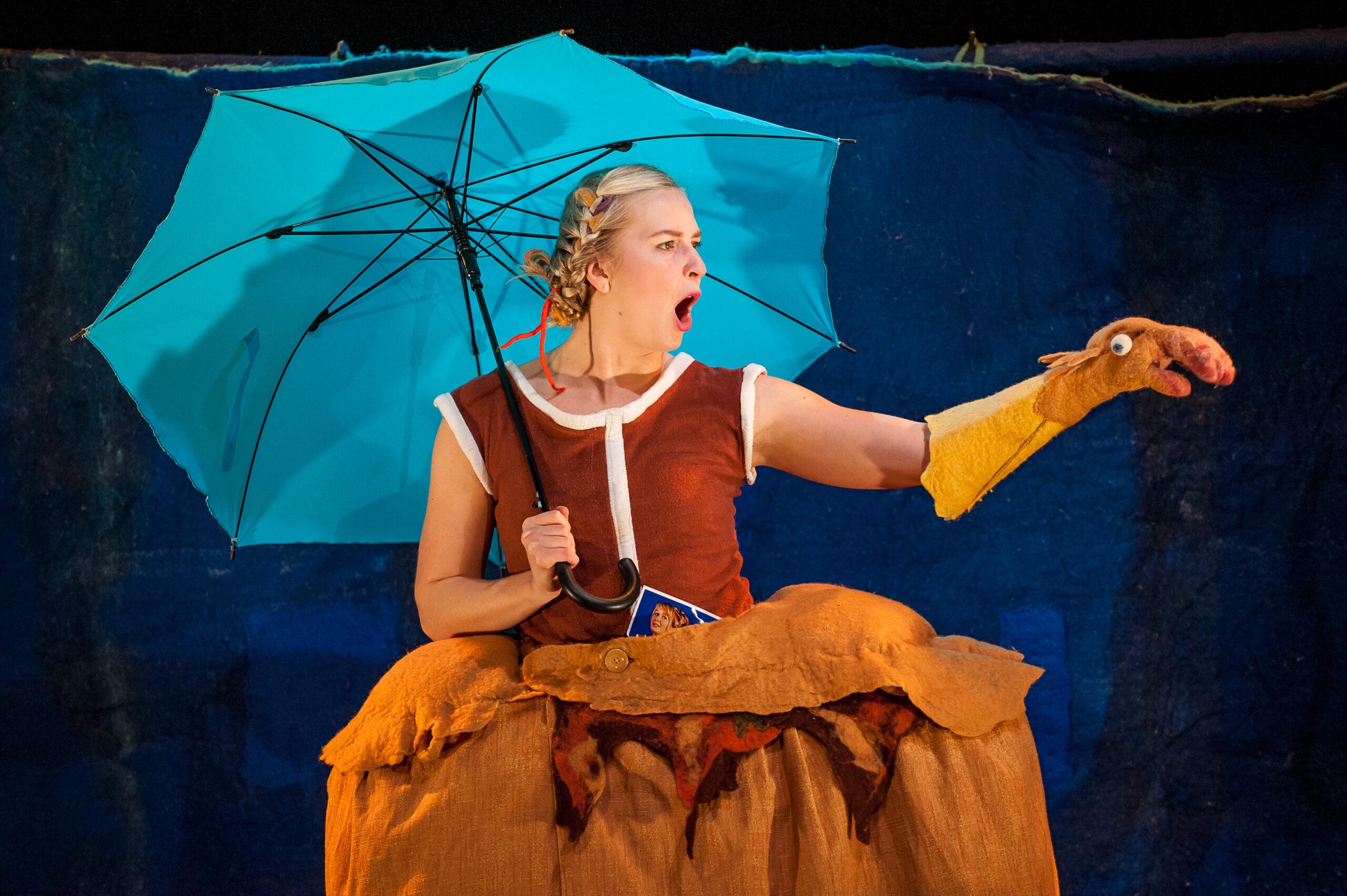 Keltahameinen näyttelijä pitelee sinistä sateenvarjoa ja näyttelee keltaisen käsinuken kanssa.