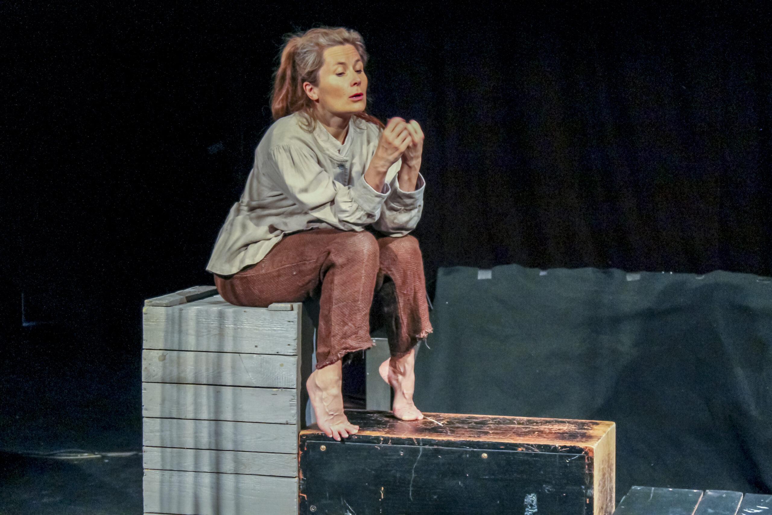 Näytteliijä istuu puulaatikon päällä huivi päässään.