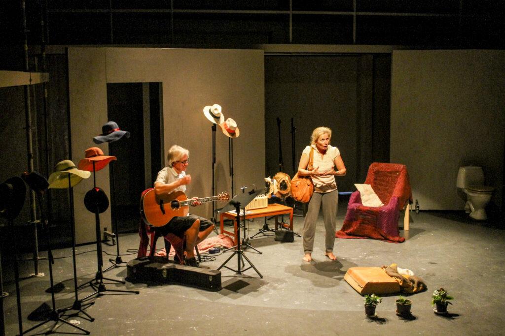 Näyttämöllä kitaraa soittava mies, nainen, huonekaluja ja hattuja.