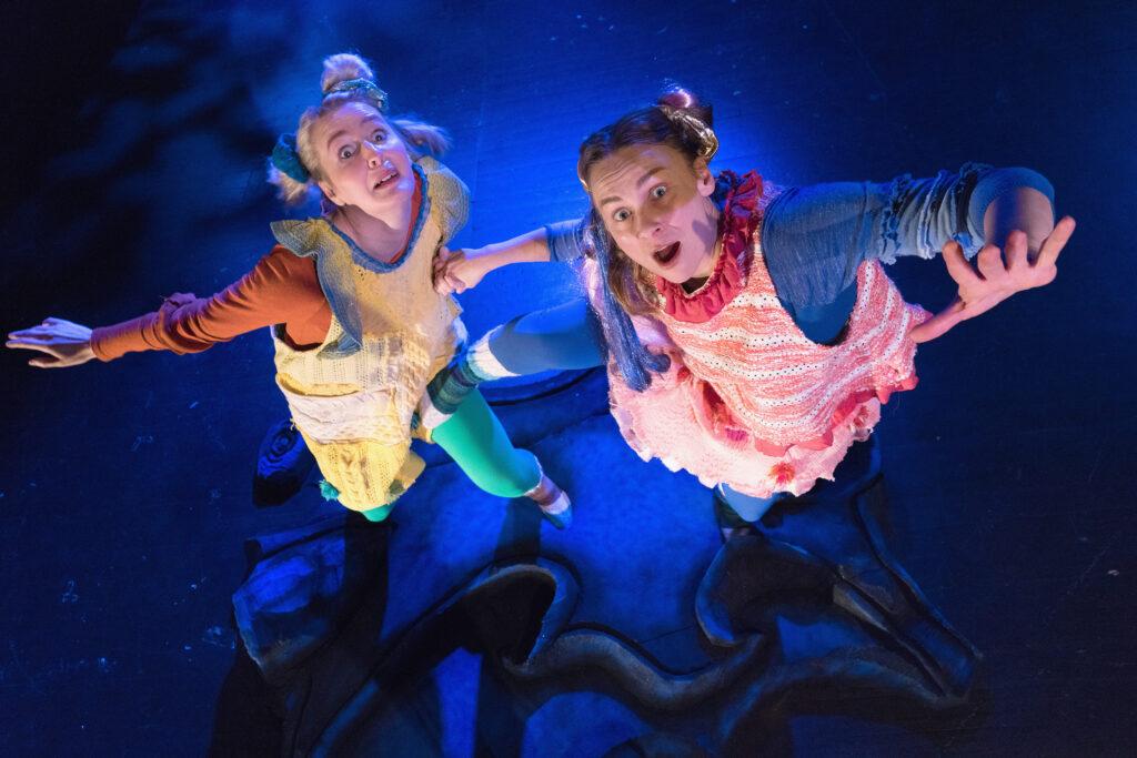 Kaksi värikkäästi puettua näyttelijää hyppivät kohti yläpuolellaan olevaa kameraa.