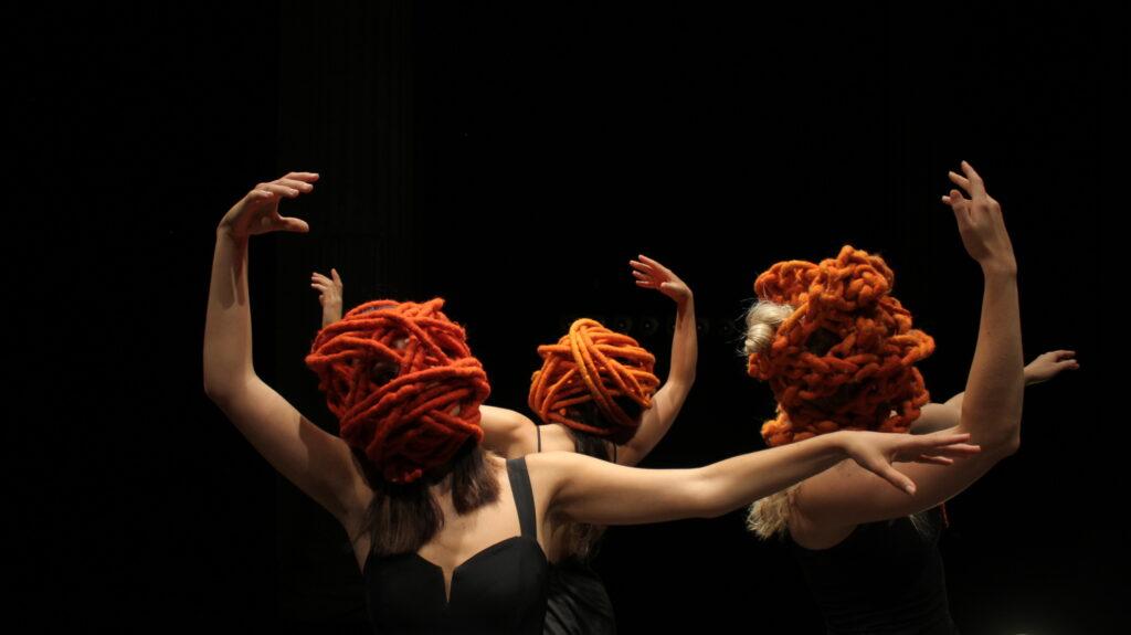 Kolme hahmoa kädet koholla oranssia huopaköyttä päänsä ympärillä.